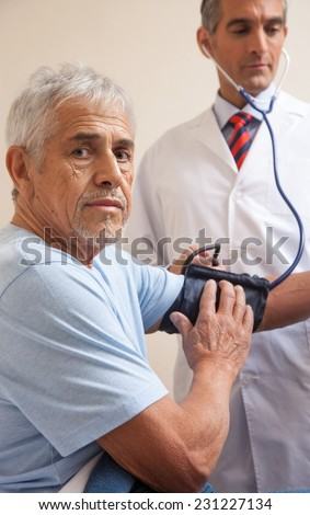 Mature man in 70s measuring blood pressure at hospital. Health concept. - stock photo