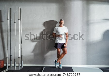 Mature man in sportswear standing alone in a gym drinking water while taking a break from a workout