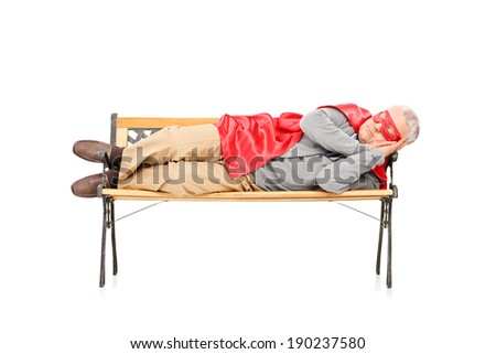 Mature man in superhero costume sleeping on bench isolated on white background - stock photo