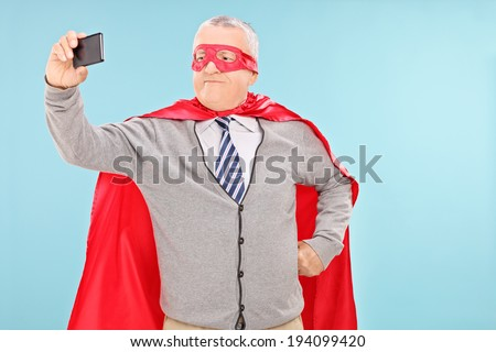 Mature man in superhero costume taking selfie on blue background - stock photo