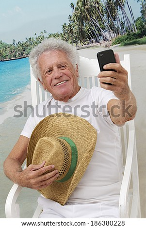 Mature man in vacation taking a picture of himself with cell phone at the tropical beach  - stock photo