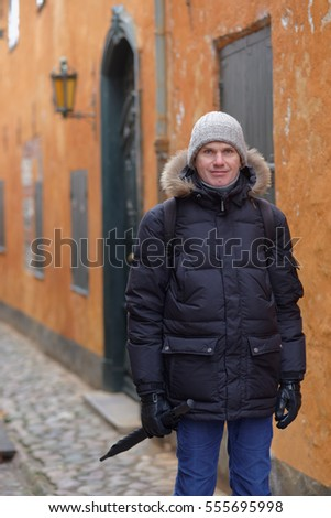 Mature man in winter clothes on a narrow street of Helsingor, Denmark