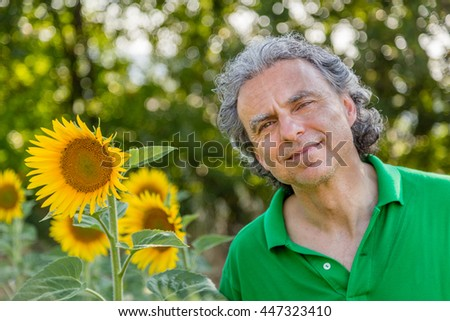 mature man is smiling winking beside of sunflowers in the countryside, nature and the outdoors make him feel happy and carefree - stock photo