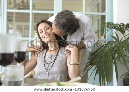 Mature man kissing woman while having a healthy lunch at home. - stock photo