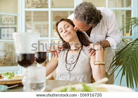 Mature man kissing woman while sitting at healthy lunch table, outdoors. - stock photo