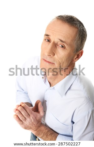 Mature man kneeling and praying to God.