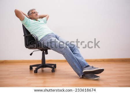 Mature man leaning back in swivel chair at home in the living room - stock photo
