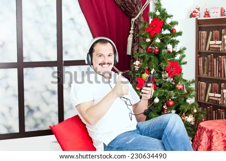 Mature man listening to music on headphones and showing thumbs up sign near christmas tree in home interior. - stock photo