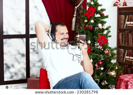 Mature man listening to music on headphones in casual wear near christmas tree in home interior . - stock photo