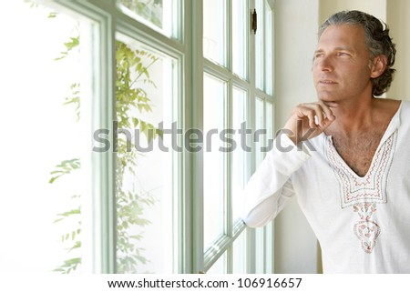 Mature man looking out a large window at home, being thoughtful.