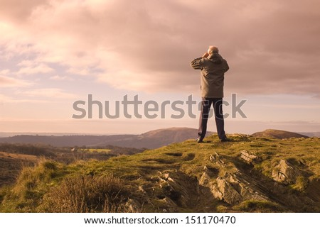 Mature man looking over mountains and hill tops through binoculars. - stock photo
