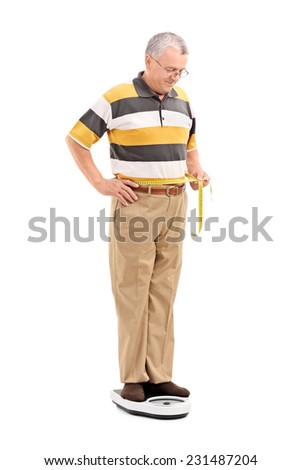 Mature man measuring his waist and standing on a weight scale isolated on white background - stock photo
