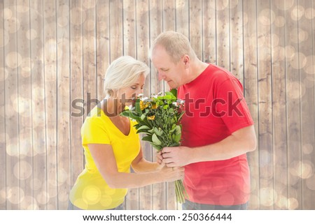Mature man offering his partner flowers against light glowing dots design pattern