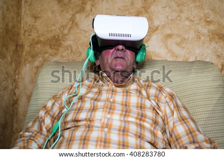 Mature man oman wearing Virtual Reality Glasses in home - stock photo