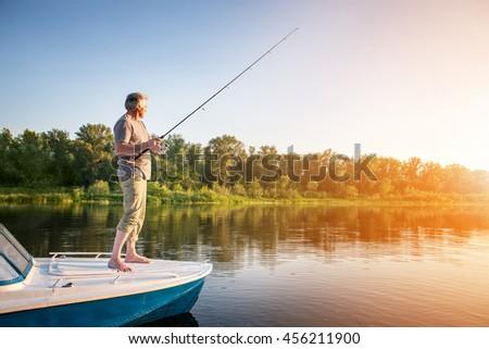 Mature man on a motor boat. Fishing - stock photo