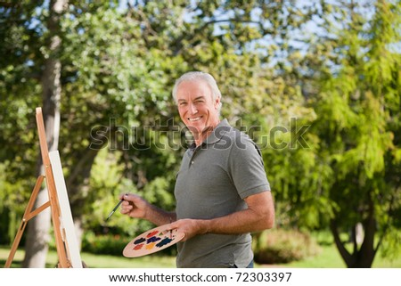 Mature man painting in the garden - stock photo