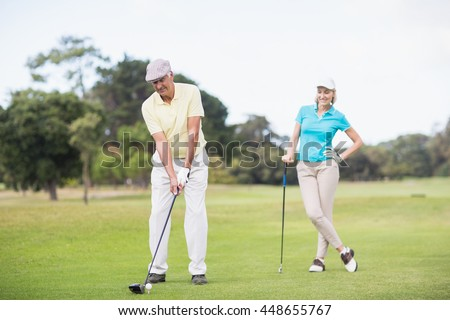 Mature man playing golf while standing by woman