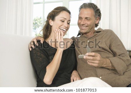 Mature man proposing marriage to a woman and offering her an engagement ring.