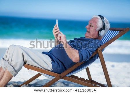 Mature man resting on a deck chair listening to music with smartphone on the beach - stock photo