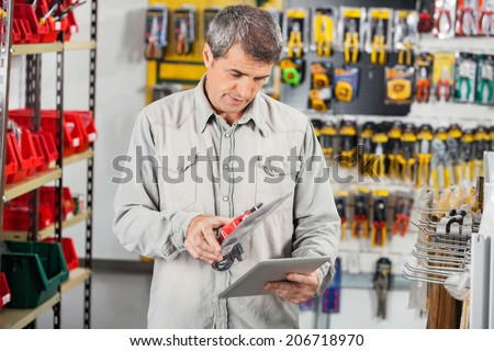 Mature man scanning product through digital tablet in hardware store