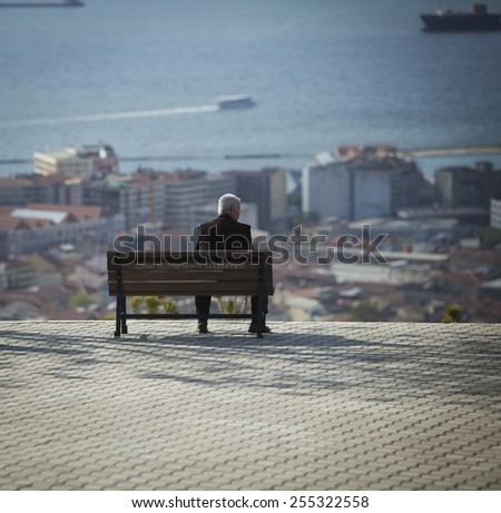 Mature man silhouetted on bench in Izmir Turkey - stock photo