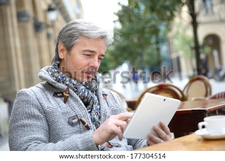 Mature man sitting at coffee shop table with tablet