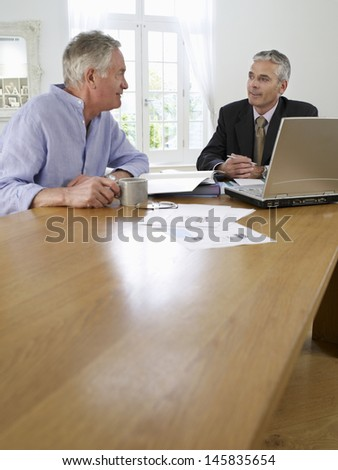 Mature man sitting at table with financial advisor - stock photo