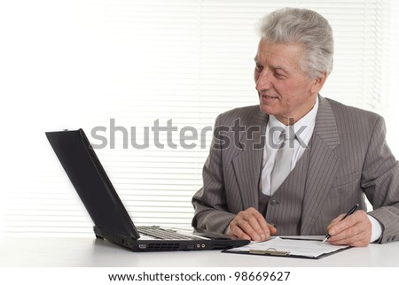 mature man sitting at the computer on a isolate