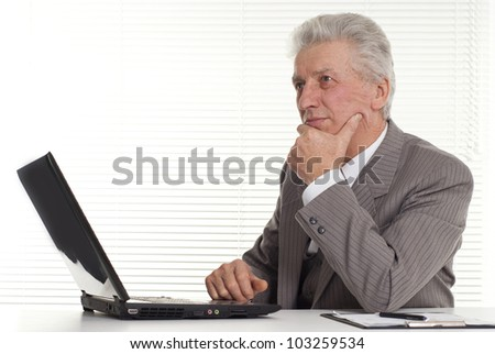 mature man sitting at the laptop on a isolate