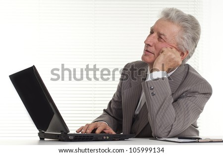 mature man sitting at the laptop on a light
