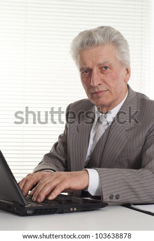 mature man sitting at the laptop on a light background