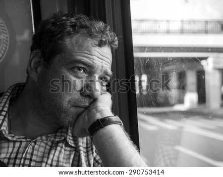 Mature man sitting at the window a public bus.  - stock photo