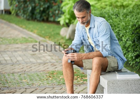 Mature man sitting on bench in park and looking at photos her made with digital camera