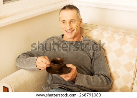 Mature man sitting on couch with cup of coffee. - stock photo
