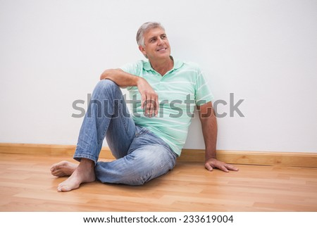 Mature man sitting on floor at home in the living room - stock photo