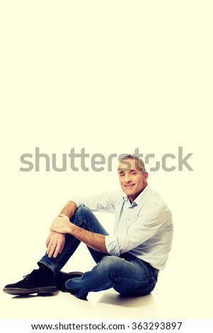 Mature man sitting on the floor