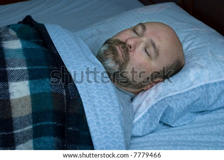mature man sleeping on back; subdued lighting with blue night cast