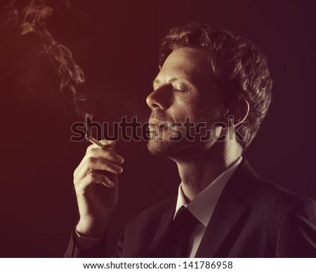 Mature man smoking cigarette against black background - stock photo