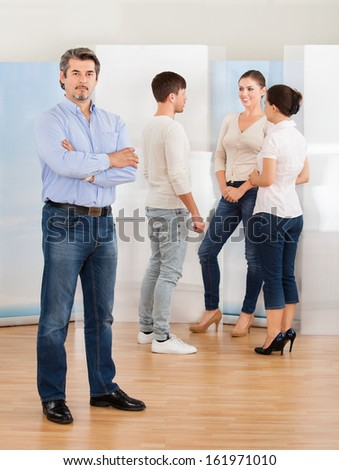 Mature Man Standing With Group Of People Discussing - stock photo