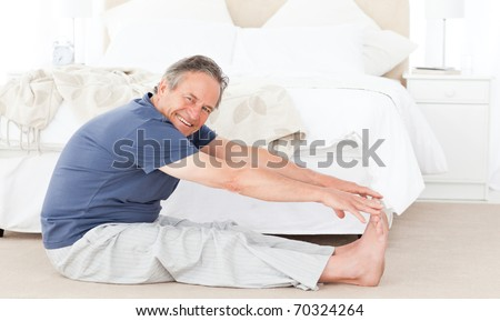 Mature man stretching in his bedroom - stock photo