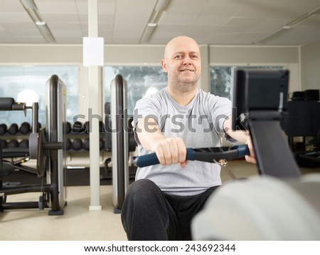 Mature man takes care of his health and he rowing in the gym