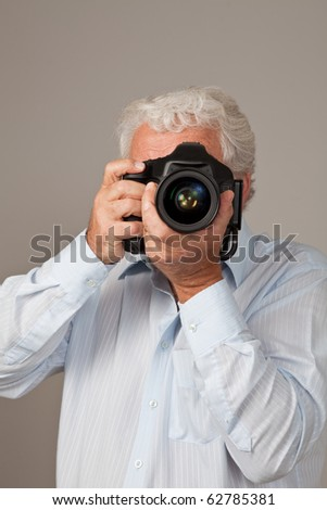 Mature man taking a picture with a single lens reflex camera. - stock photo