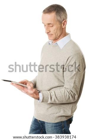 Mature man using digital tablet - stock photo
