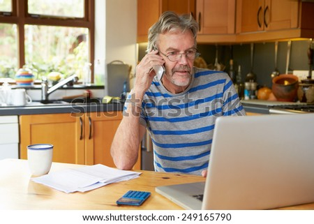 Mature Man Using Mobile Phone Looking At Home Finances - stock photo