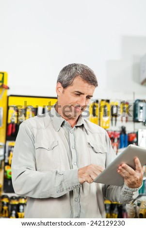 Mature man using tablet computer in hardware store - stock photo