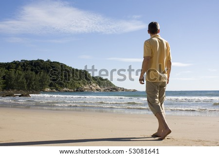 Mature man walking barefoot on a tropical beach in Brazil