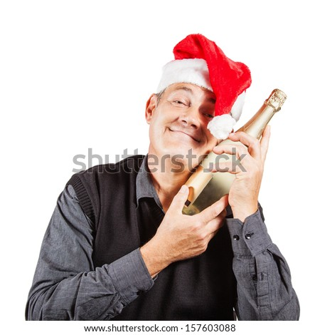 Mature man wearing Santa's hat makes a funny face while hugging a bottle of champagne - stock photo