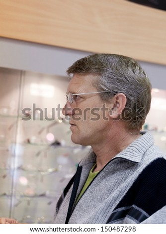 mature man wearing spectacles at a show-window with points - stock photo