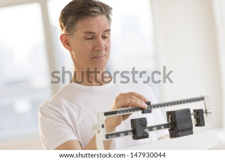 Mature man weighing himself on balance weight scale at health club - stock photo
