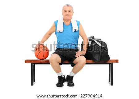 Mature man with basketball sitting on a bench isolated on white background - stock photo